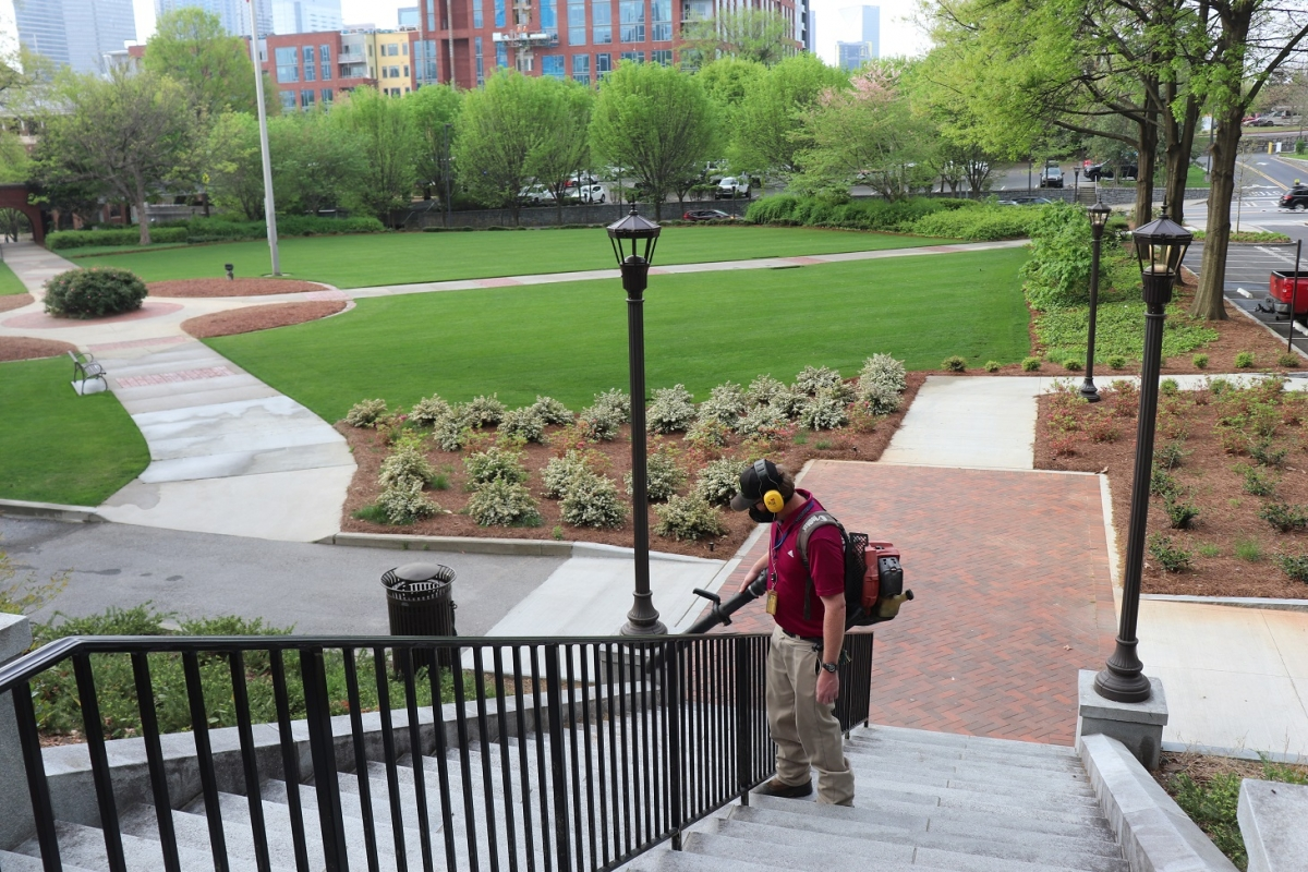 steps with landscape personnel blowing leaves with landscape in background