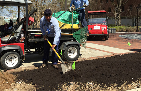 Grounds worker laying out compost in a planting bed.